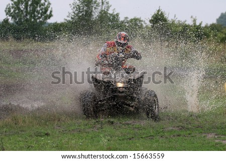 Offroad quad racer getting wet by a big splash. - stock photo