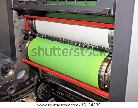 Offset press is a printing machine where the inked image is transferred from a plate to a rubber blanket, then to the printing surface. - stock photo
