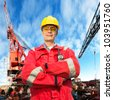 Offshore engineer, looking proudly, standing on the deck of an industrial vessel at the docks - stock photo