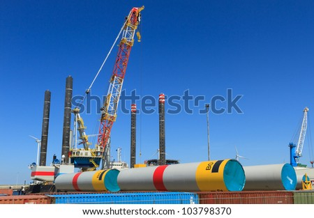 Offshore heavy lift vessel for placing wind turbines in sea, behind parts for wind turbines in a harbor. - stock photo