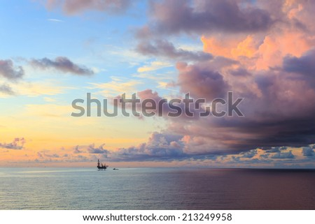 Offshore jack up drilling rig in the middle of the ocean during dramatic sunset time - stock photo