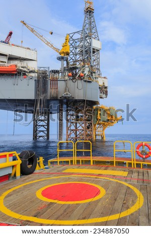 Offshore Jack Up Drilling Rig Over The Production Platform in The Middle of The Sea View from Crew Boat - stock photo