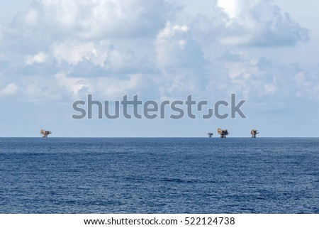 Offshore oil and gas wellhead remote platform blue sea and cloudy sky over it