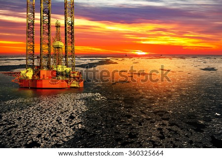 Offshore oil and rig platform in sunrise on frozen sea. - stock photo
