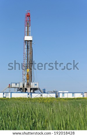 offshore oil drilling rig on green wheat field