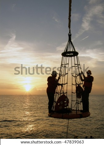 Offshore oil field workers being lowered from the rig to a boat below - stock photo