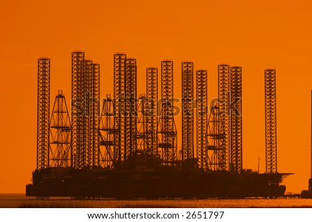 Offshore oil rig at shallow waters during sunset - stock photo