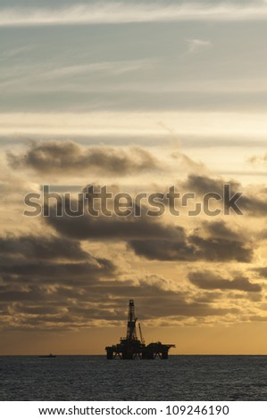 offshore oil rig at sunset/sunrise cloudscape - stock photo