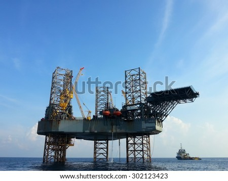 offshore oil rig drilling platform and small ship with blue sky