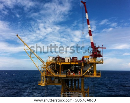 Offshore production platform with dramatic blue sky