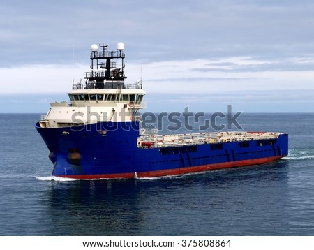 Offshore Supply Vessel underway at sea to offshore facility. - stock photo