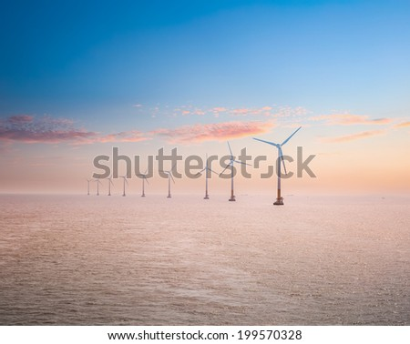 offshore wind power plants in sunset , clean energy background  - stock photo