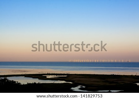 Offshore wind power station in sunrise