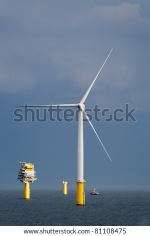 Offshore wind turbine and a transformer substation in a windfarm under construction of the Norfolk Coast, North Sea - stock photo