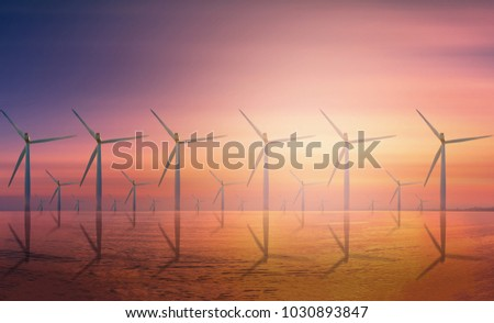 Offshore Wind Turbine in a Wind farm under construction off coast at sunset.