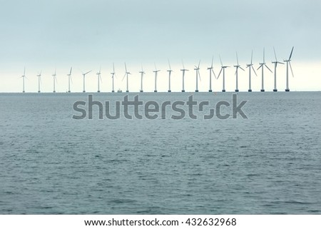 Offshore wind turbines in cloudy weather - stock photo