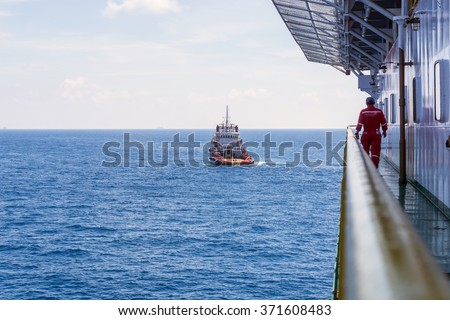 Offshore worker walking on the walkaway on board construction barge monitoring anchor handling operation at Terengganu oilfield, Malaysia