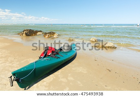 "Ogunquit, Maine - August 27, 2016: A Green Kayak Docking on the Ogunquit Beach, Maine. Ogunquit was named by the Abenaki tribe, because the word means ""beautiful place by the sea"""