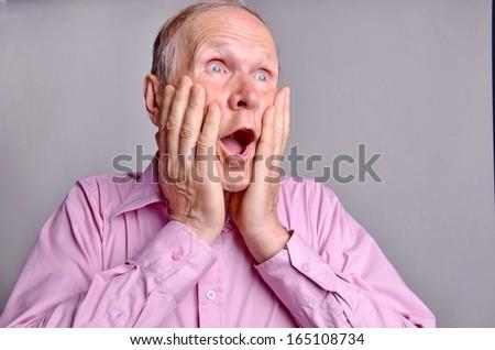 Oh my God! What I did! Amazed mature man portrait on grey background  - stock photo