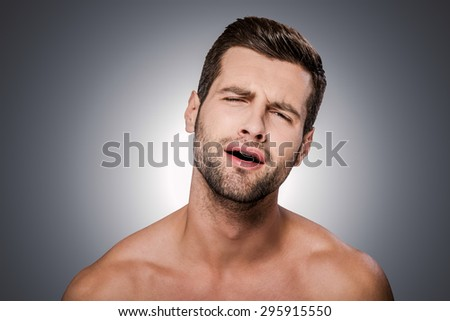 Oh no! Portrait of frustrated young shirtless man looking at camera and grimacing while standing against grey background - stock photo