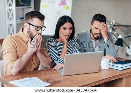 Oh no! Three frustrated young business people in smart casual wear looking at the laptop and expressing negativity - stock photo