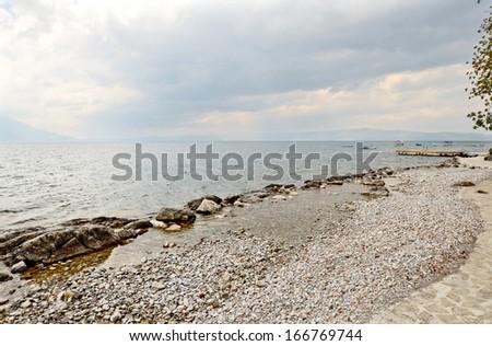 OHRID, MACEDONIA, MAY 18, 2011. Rocks and rocky sand in the shoreline of lake Ohrid. - stock photo