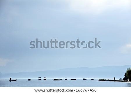 OHRID, MACEDONIA, MAY 18, 2011. Silhouettes of boats in lake Ohrid. - stock photo
