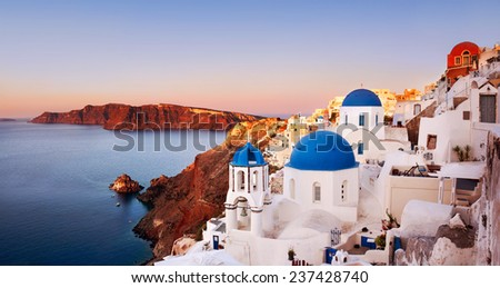 Oia at sunrise with caldera view in Santorini, Greece. Focus on Blue Domes. - stock photo