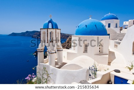 Oia Orthodox churches and the bell tower on Santorini island, Greece.