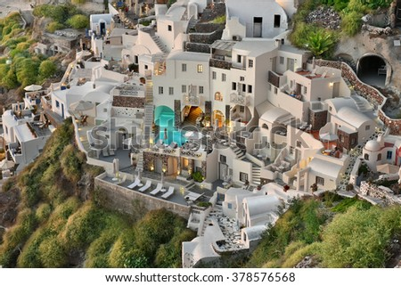 OIA, SANTORINI, GREECE - OCT. 2015: The famous Cycladic Architecture cave houses which are used as motels and inns built on cliffs in the town village of Oia, Santorini, Greece. - stock photo