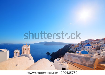 Oia town on Santorini island, Greece. Traditional and famous houses and churches with blue domes over the Caldera, Aegean sea. Wide angle view - stock photo