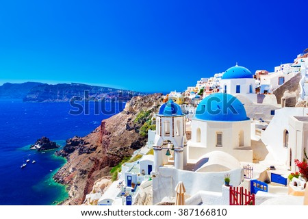 Oia town on Santorini island, Greece. Traditional and famous houses and churches with blue domes over the Caldera, Aegean sea - stock photo