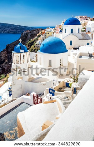Oia town on Santorini island, Greece. Traditional and famous white houses and churches with blue domes over the Caldera, Aegean sea - stock photo