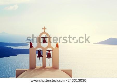 Oia town on Santorini island, Greece. Traditional bells and cross over the Caldera, Aegean sea - stock photo