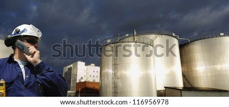 oil and fuel storage tanks with worker in foreground, sunset and panoramic view - stock photo