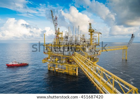 Oil and gas central processing platform in the gulf of Thailand. Construction crane transfer cargo to boat. - stock photo