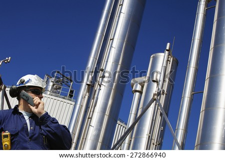 oil and gas engineer with large gas-pipes pipelines in the background - stock photo
