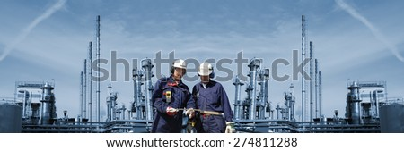 oil and gas engineers with large refinery in background, panoramic view - stock photo