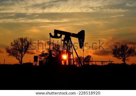 Oil and gas industry: oil pump jack on a oil field in sunset - stock photo