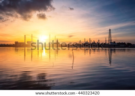 Oil and gas industry - refinery at Sunrise - factory - petrochemical plant  with reflection over the river - stock photo