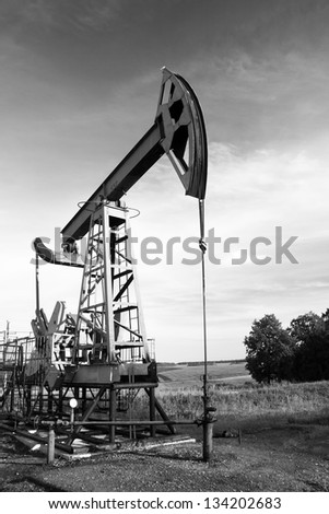 Oil and gas industry. Work of oil pump jack on a oil field. Black and white photo
