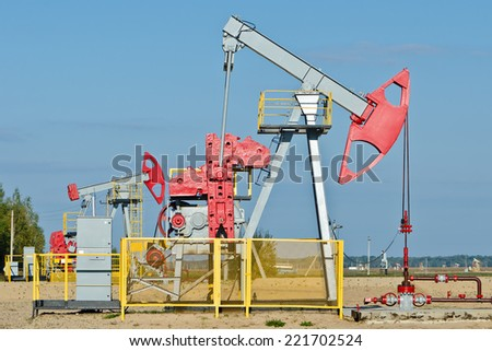 Oil and gas industry. Work of oil pump jack on a oil field. First pump in focus. - stock photo