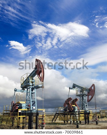 Oil and gas industry. Work of oil pump jack on a oil field. White clouds and blue sky - stock photo
