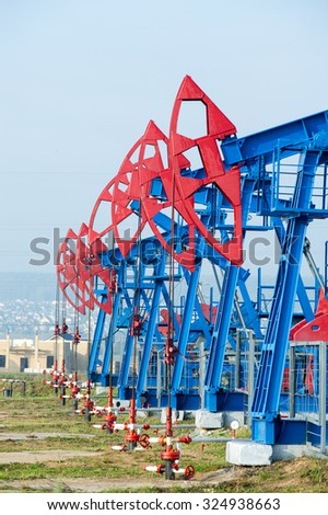 Oil and gas industry. Work of oil pump jack on a oil field. White clouds and blue sky. oil well pump. Oil and gas industry. Work of oil pump jack on a oil field.