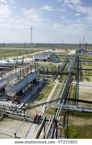 Oil and gas industry. Work of refinery petrochemical plant. Oil reservoir and storage tank of mineral oil. Blue sky above factory - stock photo