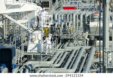 Oil And Gas Industry. Work on the gas tanker safety monitor. industrial. Workers on gas tankers - stock photo