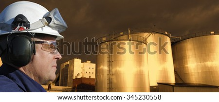 oil and gas industry, worker in close-ups with giant fuel-storage tanks, sunset time - stock photo