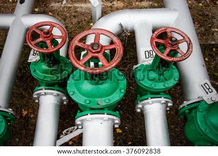 Oil and gas pipe line and old green valves - stock photo
