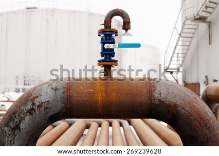Oil and gas pipeline valve on rusty piping - stock photo