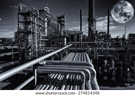 oil and gas refinery under a large full moon, night-time image - stock photo